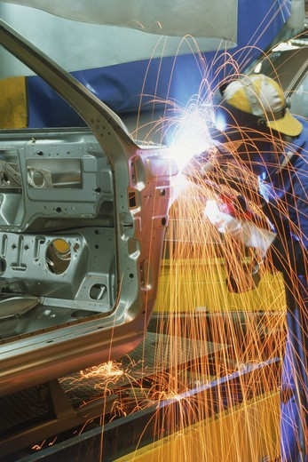Sparks flying off metal sander at automobile factory : Stock Photo