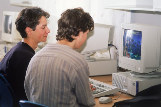Teenage students at keyboard in high school computer class : Stock Photo