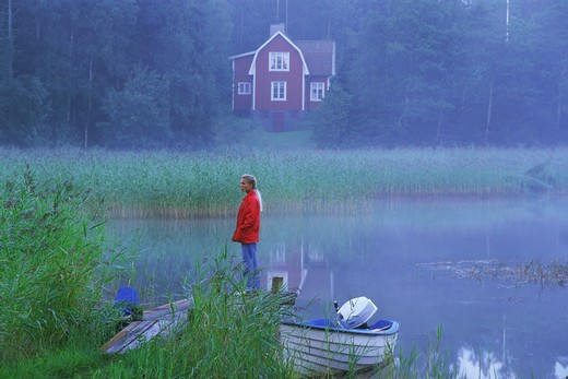 Stock Photo: 4286-28524 Woman standing on lake pier in evening mist in Sweden
