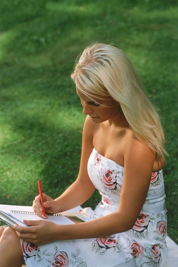 Stock Photo: 4286-28626 Young lady reading and writing outside in summer dress
