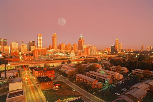 City skyline, apartment buildings and roads around Atlanta under full moon at dusk : Stock Photo