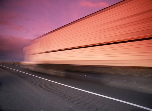 Truck and trailer speeding along California highway reflecting sunset light : Stock Photo
