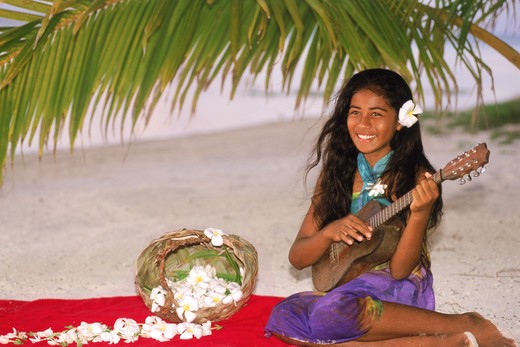 Stock Photo: 4286-28940 Polynesian girl sitting on Aitutaki beach under plam frond playing ukelele
