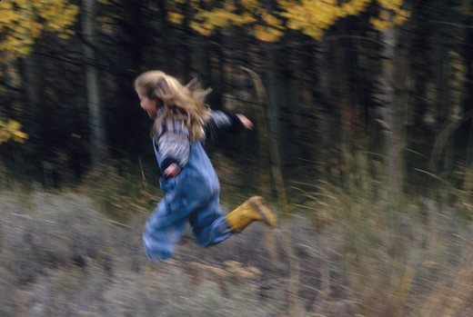 Stock Photo: 4286-29109 A young girl runs through a field by a woods.
