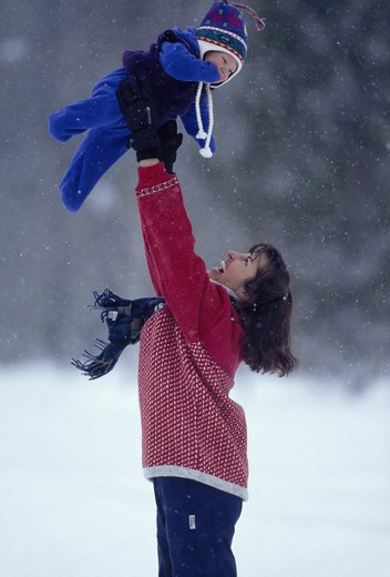Stock Photo: 4286-29130 A mother lifts her baby high over her head while standing outdoors on a lightly snowing day.