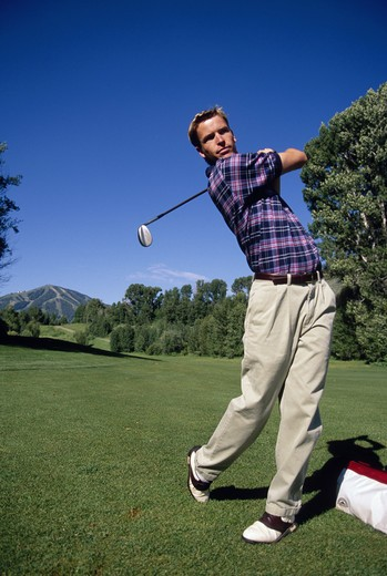 A golfer has just swung at the ball on a golf course.  : Stock Photo