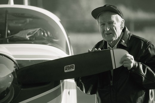 A senior man examines the edge of the propeller to his single engine private plane. : Stock Photo