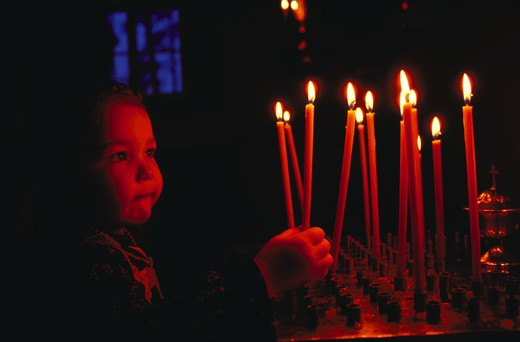 Young girl worshipper with candles, Orthodox Church, Joensuu, Finland.  30,000 plus total European images. : Stock Photo