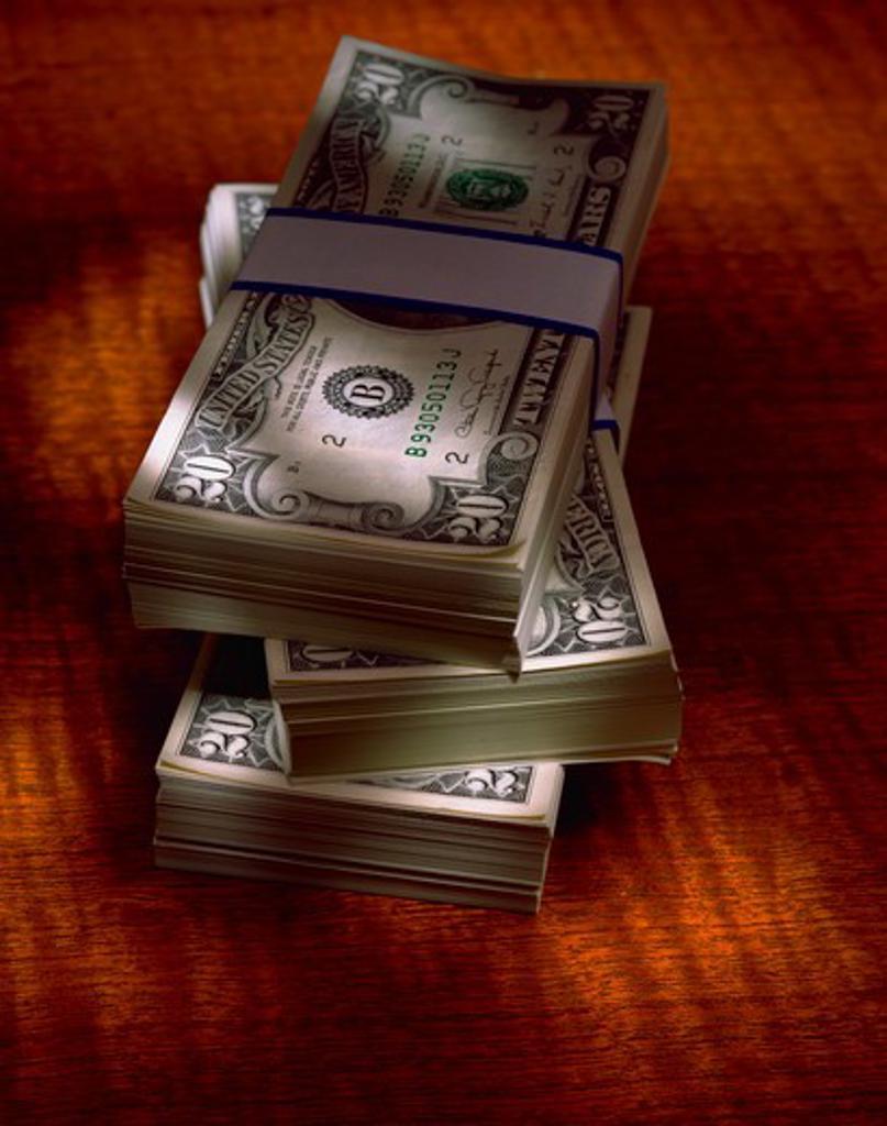 Stock Photo: 4286-29597 Still-life; 3 bundles of money on orange background