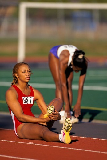 Stock Photo: 4286-29608 Two African-American women track runners stretch before the start of a race.