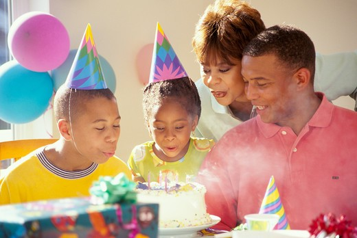Stock Photo: 4286-29643 African-American family celebrating their son's birthday as both he and his sister blow out the candles.