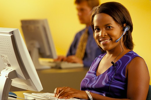 Stock Photo: 4286-29645 African-American woman wearing a head set while working on her computer and her  male coworker can be seen in the background.
