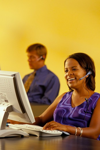 Stock Photo: 4286-29646 African-American woman wearing a head set while working on her computer and her  male coworker can be seen in the background.