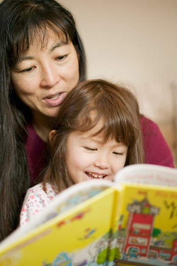 Stock Photo: 4286-29669 Close-up of mother  reading a book to her young daughter both of Asian ethnicity.