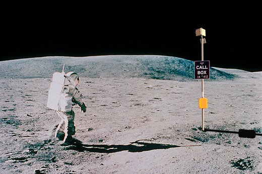 Astronaut in a space suit on the surface of the moon walking toward a telephone call box. : Stock Photo