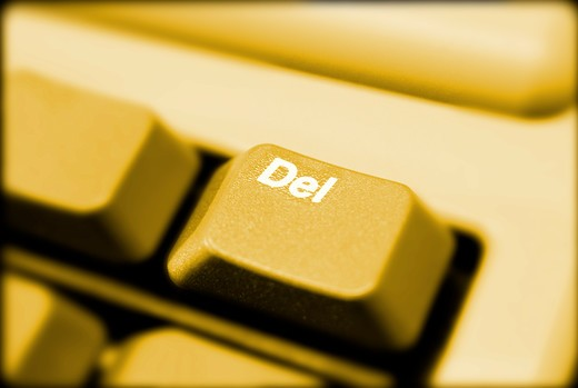 Close-up of 'Delete' key on computer keyboard with yellow light. : Stock Photo