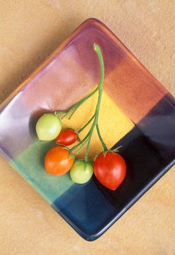 Stock Photo: 4286-30114 Stem of tomatoes on a colorful dish