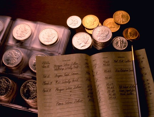 Gold and silver coins with stamp collecting ledger and collector?s album. : Stock Photo