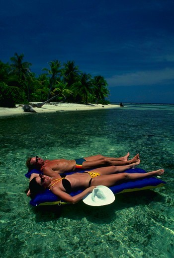 Stock Photo: 4286-30449 Couple on air mattresses in a lagoon in the Caribbean.