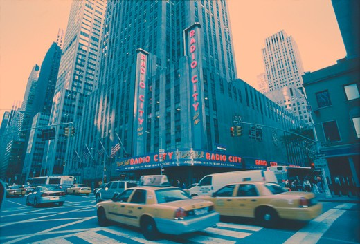 Stock Photo: 4286-30561 Taxis and vans pass through the intersection of Sixth Ave. & 50th St. in front of Radio City Music Hall, New York City.