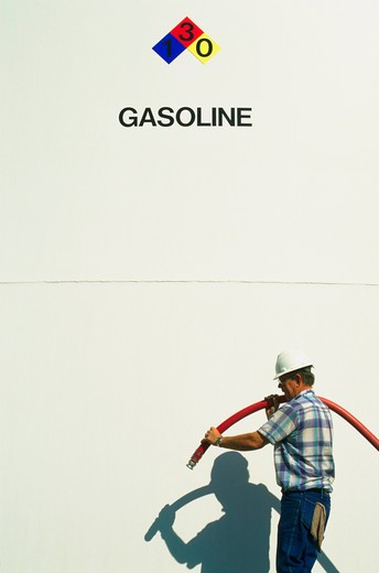 Stock Photo: 4286-30667 Refinery employee by gasoline storage tank.