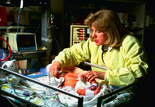 Neonatologist cares for infant in hospital neo-natal intensive care unit (NICU). : Stock Photo