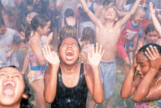 Stock Photo: 4286-30755 Children react to firehose spray. Summer shower.