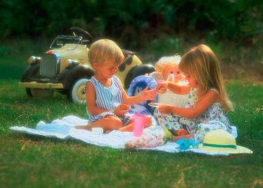 Stock Photo: 4286-31038 A young boy and girl, age three, sitting on a blanket in the grass having a tea party with a miniature car in the background.