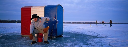 Stock Photo: 4286-31153 Ice fisherman reeling in line on frozen lake, St. Paul, MN. Red, white and blue ice shack behind him.