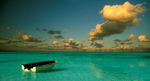 A lone rowboat moored in calm blue water with dark clouds against an erie sky, Isla Mujeres, Mexico. : Stock Photo
