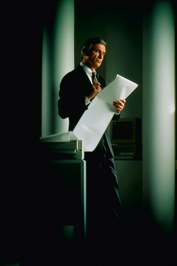 Stock Photo: 4286-31233 Businessman reviewing printout