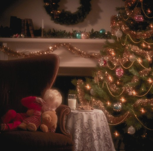 Stock Photo: 4286-31257 Young boy sleeping next to Christmas tree waiting for Santa Claus.