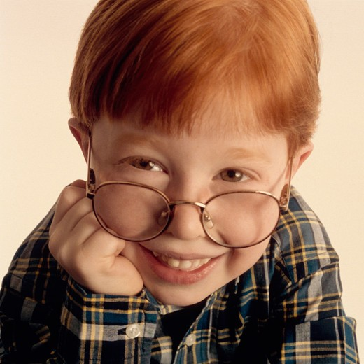 Portrait of young boy with red hair and glasses. : Stock Photo