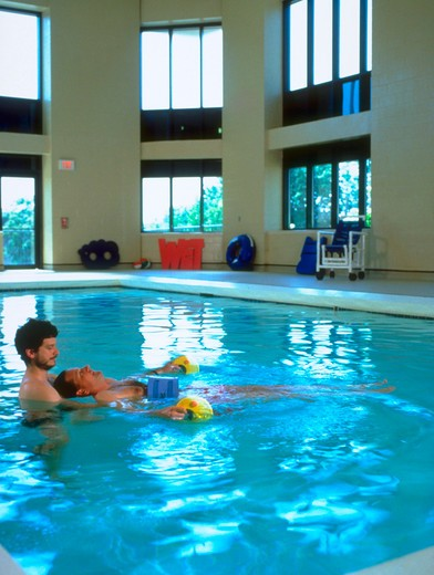 Male rehabilitation specialist doing therapy with a patient in a swimming pool. : Stock Photo
