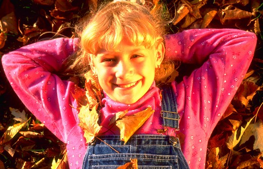 Portrait of a young blond girl lying in a pile of fall leaves. : Stock Photo