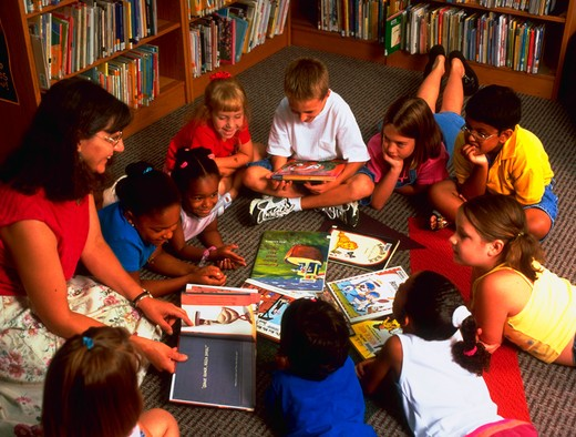 Ten young children sitting and laying on the floor in a circle as an adult teacher reads to them from a book. : Stock Photo