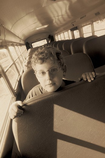 Black and white close-up of a child leaning forward on a bus seat looking disappointed or sad.  : Stock Photo