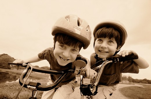 Stock Photo: 4286-31435 Close-up of twin boys who are wearing helmets while riding their bicycles.