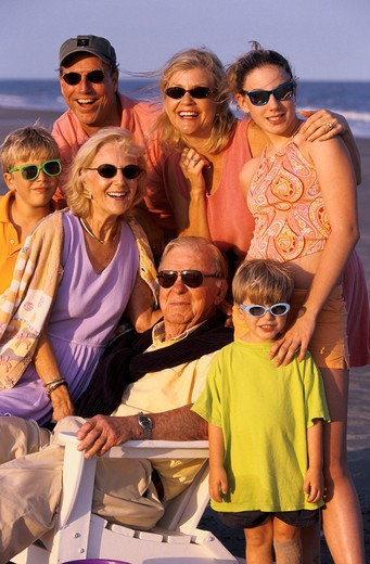 Portrait of an extended family joined together at the beach including parents, grandparents and children. : Stock Photo