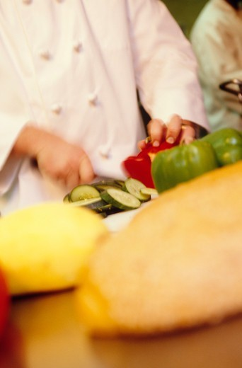 Stock Photo: 4286-31540 A chef prepares food at a restaurant, cutting cucumbers and peppers amongst other vegetables.