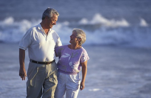 Casually dressed mature couple smile at each other as they walk together along the beach as surf crashes in the background. : Stock Photo