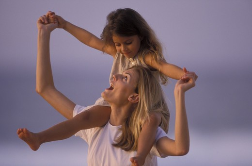 Stock Photo: 4286-31681 Woman looks up at the young daughter she is carrying outdoors on her shoulders.