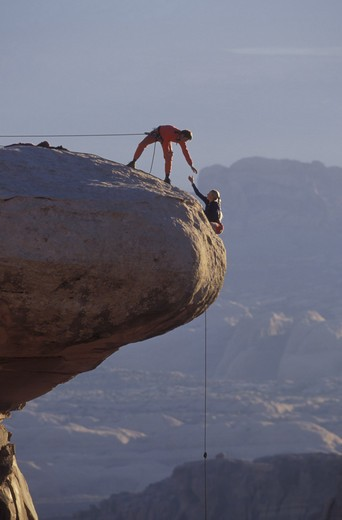 Male climber on a safety rope reaches out to a female climber as she makes her way up and over an outcrop of rock at the summit. : Stock Photo