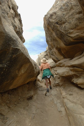 Chaco Canyon, New Mexico. Chaco Culture National Historic Park. Visitor hiking through the rocky cliff trail that leads to the Pueblo Alto ruins.  Ruins of dwellings of Ancient Puebloan peoples. Commerce center and spiritual meeting place. : Stock Photo
