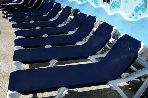 Stock Photo: 4286-31999 Deck chairs at at a hotel pool, Puerto Vallarta, Mexico