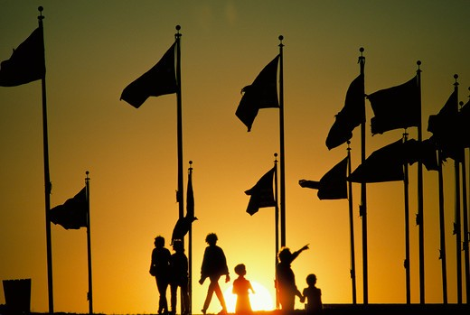 Stock Photo: 4286-32079 Tourists and flags on the grounds of the Washington Monument are silhouetted by the setting yellow sun.