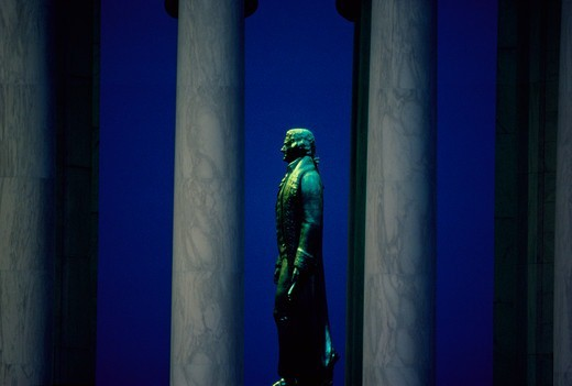 Bronze statue of Thomas Jefferson seen in profile between the columns of the Jefferson Memorial, Washington, DC. : Stock Photo