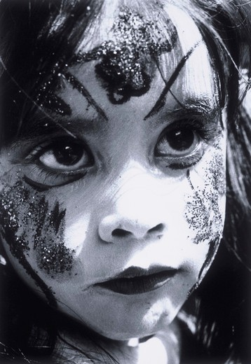 Close-up portrait of a young girl with her face painted with clown make-up and glitter. : Stock Photo