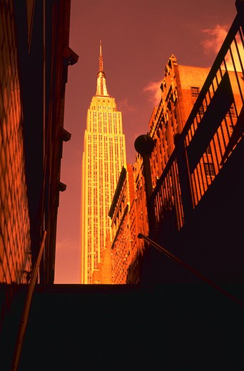 View of the Empire State Building in New York City illuminated in gold light as seen from a subway exit stairway. : Stock Photo
