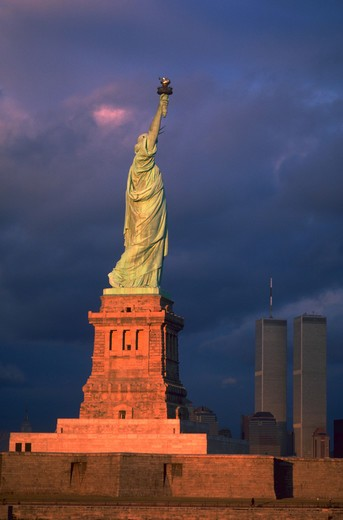 Stock Photo: 4286-32423 View of the back of the Statue of Liberty in New York with the World Trade Center Towers in the background against a cloudy sky.
